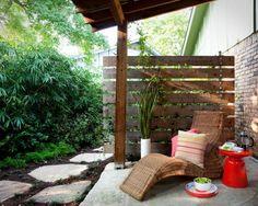 terrasse avec palissade en bois et chaise longue en rotin