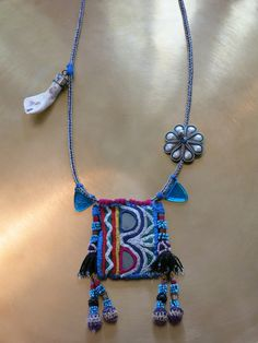 """Kinship Stories: Ethnic necklace whose base is made of a sterling silver chain. The centerpiece is made with vintage Rabari embroidered fabric from an old blouse. Attached to it are vintage Uzbek tassels, originally part of a headdress. The silver flower is an old Yemeni mixed silver piece. The triangles are Afghani glass beads. The tooth is a bovine tooth. It is worn in countries like Nepal as part of the """"medicine necklace."""" This necklace is entirely handmade and a unique item."""