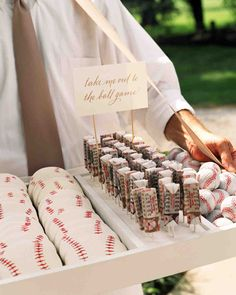 take me out to the ballgame... If the two of you spend lots of time rooting for your team, why not make America's favorite pastime your wedding's motif? Some ideas: Design the invitations to look like tickets to a game, order a wedding cake shaped like a stadium, and use pro baseball team pennants instead of table numbers. Home run! {baseball}