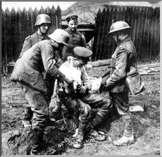 A German soldiers dresses a wounded British soldier