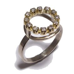 This ring is a little traditional, a little funky. The band is made of 950 Palladium and the setting is 14K yellow Gold. 12 white diamonds make .18 total carat weight. The circle measure approximately