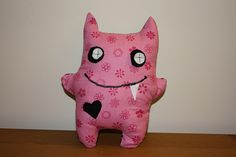 Adorable monster plush! Love the felt circles stitched on in a cross for the eyes and the little heart appliqué.