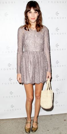 Alexa Chung in a lace Lover cocktail dress. A straw tote and metallic Mary Janes competed the look.