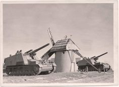 """Two German """"Hummels"""" and a windmill. The Hummel (""""bumblebee"""") was a self-propelled artillery gun based on the Geschützwagen III/IV chassis and armed with a 150mm howitzer. It was used by the German Wehrmacht from early 1943 until the end of the war."""