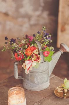 I think this is a great idea and looks cute. Using old tin watering cans and filling with flowers would make a great centrepiece you could always tie your table number on with lace or string.