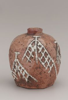 Faceted candy-pellet bottle with design of drying nets, unkown Raku ware workshop 19th century, Edo period or Meiji era.Earthenware with Red Raku glaze and white slip.   Edo period or Meiji era   Earthenware with ...