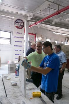 Local 7 NY/NJ marble apprentice Brandon Muniz, front, prepares to cut a marble slab with guidance from instructor Victor DeSalvo. Behind them, Local 7 NY/NJ Secretary-Treasurer Chris Guy, left, and President Tom Lane discuss shop renovations.