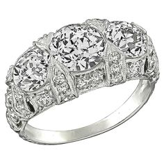 Edwardian Cushion Cut Diamond Platinum Ring. This stunning platinum ring from the Edwardian era, is centered by two sparkling cushion cut diamonds weighing approximately 1.90ct. The color of these diamonds is H-I with VS2 clarity. The center diamonds are accentuated by dazzling round cut diamonds weighing approximately 0.75ct. and are graded H color with VS clarity. The top of the ring measures 10mm by 15mm.