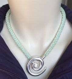 Beaded Kumihimo cord necklace with foil beads on cool mint cord with swirl clasp.    Kumihimo jewelry by N. Stapley Designs
