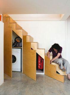"""Nesse caso, a utilidade falou mais alto. No interior da escada, foi possível """"esconder"""" a máquina de lavar roupa, além de alguns outros objetos que o morador não usa com tanta frequência, como malas, por exemplo."""