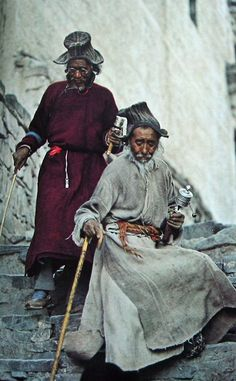 """Spinning their way with each step, two elderly pilgrims pick their way down from Hemis Gompa. The devout believe that each revolution of the scripture-filled copper wheels sends supplications heavenward."" Photograph by Thomas J. Abercrombie for National Geographic, March 1978."