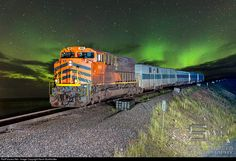The ArcelorMittal Quebec Cartier Mining Corporation's weekly employee passenger train from Port Cartier to Mount Wright, Quebec, to service all of the online camps and the Fire Lake raw ore mine as well as the Mount Wright processing plant, is seen along Petit-Lac-Manicouagan with intense Aurora Borealis activity ALL over the sky. Calling it the northern lights during this trip would be a misnomer as they were frequently well south of our locations. The train consists of a HEP car, a…
