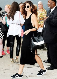 Lily Aldridge wears a black midi dress, round sunglasses, Adidas sneakers, and a black and white backpack