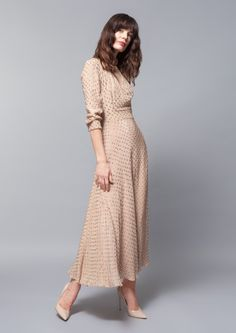 A nude beige ankle length dress in matte silk with shiny dots in the same hue. A shawl collar and three quarter length sleeves fitted at the waist with a a line skirt flowing down. Simply elegant by Alexander Terekhov.