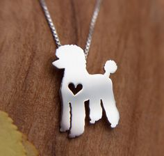 "This tiny Poodle necklace is a perfectly delicate way to keep a loved pet close to your heart. Approximately ⅝"" at its largest dimension, our pendants are made by hand with love.  This pendant is cut, soldered, finished, and polished completely by hand. It comes with a delicate sterling silver box chain, and is packaged in a gift box. If you are purchasing this item as a gift and would like a short note included, please add your text in the note to seller at checkout…"