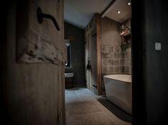 Landelijke badkamer met grijstinten i.c.m. hout, houten deuren en wit ligbad. #badkamer #landelijk #bad #bathroom #rustic #bath #tub