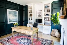 home office study with black panelled walls, and built-in white cabinet with shelves and desk for computer, antique wooden desk