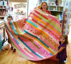 Alicia & family helpers holding her newly completed and very fun 1600 quilt!