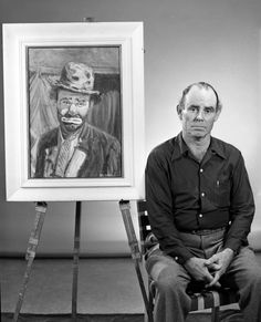 """Emmett Kelly sitting next to a painting of him as the clown """"Weary Willie"""" by circus artist Ray Wolfe. Photo by Joseph Janney Steinmetz."""