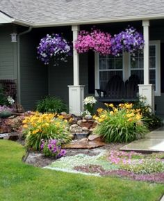 DIY front landscaping with 5 tier waterfall. A mixture of perennial and annual flowers keep the flowerbed looking lush all summer and is an inexpensive way to add curb appeal. The black adironack style front porch swing that we built serves as the perfect place to sip lemonade and enjoy the blooms! |Pinned from PinTo for iPad|