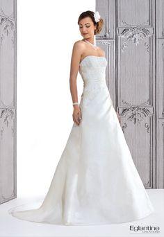 Schickes Kleid aus Seide mit Guipüre-Spitze. Die Trapezform und die Seidendrapierungen geben diesem Brautkleid-Modell einen Couture-Stil.