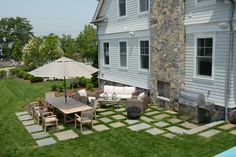 """Random square  rectangle bluestone pieces  with 6"""" grass joints create this patio with outdoor fireplace."""