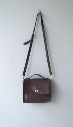 Classic vintage Coach Court bag in dark brown with brass hardware, top handle, outer pocket, brass hardware and long, adjustable, cross-body strap.  --- M E A S U R E M E N T S ---  10 x 10 3 wide base 44 long strap maker/brand: Coach   serial No. D5S-9085 condition: some wear, mostly to the edges  ➸ More vintage bags http://www.etsy.com/shop/DearGolden?section_id=10308208  ➸ Visit the shop http://www.DearGolden.etsy.com _____________________  ➸ instagram   deargolden ➸ twitter   deargolden…