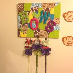 Hair Bow holder:  I covered a canvas with a collage of scrap paper to match the room decor. The collage was sealed using modge podge. Finished off with letters on the front, and ribbon tacked to the back, and now I have a place to hang all the bows I've made for my girls.