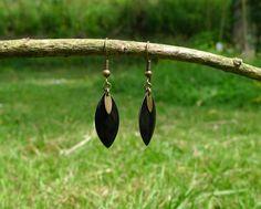 Boucles d'oreilles composées d'une navette émaillée noire et d'une petite navette métallique bronze. S'attachent par un crochet d'oreille sans nickel et sans plomb. Ha…