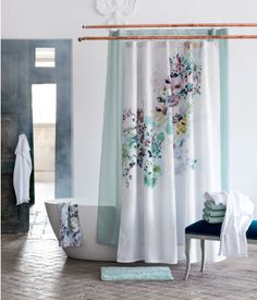 Floral shower curtain with a turquoise bath mat | H&M Home
