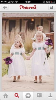 Flower girls in ivory dresses with duck egg blue sashes carrying a single stem purple headed flower