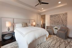 David James Custom Builders - Lovely bedroom features tray ceiling accented with pot lights and modern ceiling fan over cream leather extended headboard with nailhead trim framing queen bed dressed in white and cream border bedding flanked by cut-out cube nightstands atop Beni Ourian Rug.