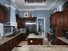 I like this wall color, and it's nice that the floor is lighter than cabinets. Floor is too light for me but still. (Blue gray kitchen with dark cabinets in Grey Oaks, Naples, Florida)