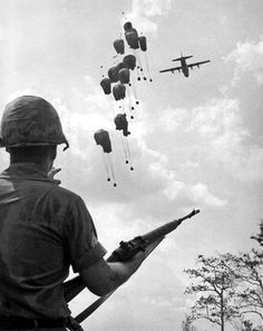 A U.S. soldier with an M14 watches as supplies are dropped in Vietnam 1967.
