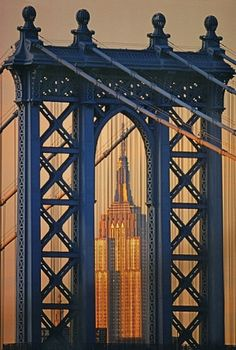 The Empire State Building is framed in arch of The Manhattan Bridge in New York City