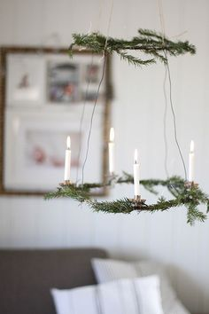 Simple holiday chandelier with greenery and candles.