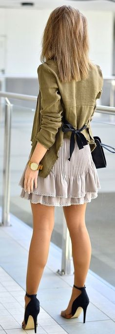 Olive green jacket with a black bow styled with a pleated grey skirt and black heels
