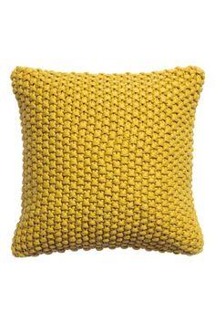 Capa almofada ponto de arroz: Capa de almofada com parte da frente em malha de ponto de arroz e parte de trás em tecido. Tem fecho éclair oculto.
