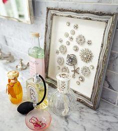 sua coleção de broches exposta numa moldura que também enfeita a bancada do banheiro