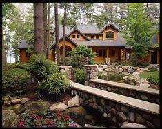 Tucked back in a gorgeous wooded alcove, this cedar log cabin is accented by a delightful stone pathway and small stone bridge.