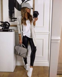 Fashion blogger mia mia mine pulls together a casual cute gym outfit for the fall. To get the look, pair a v-neck tee with some faux leather leggings and finish the look with white adidas swift run sneakers. Transition this outfit to the streets by throwing on a cozy cardigan and a baseball cap. #athleisure #leggingsoutfit #casualootd