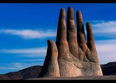 """It looks like the extremity of a giant man, buried by a monumental sandstorm. In the wasteland of Chile's Atacama Desert, 75 km to the south of the city of Antofagasta, a strange & unexpected sight confronts the eye: 4 fingers, a thumb & part of a palm, emerging from the sand. Set against the azure sky, this surreal giant hand is of course not made of flesh but stone. Called """"Mano de Desierto""""/""""Hand of the Desert"""""""