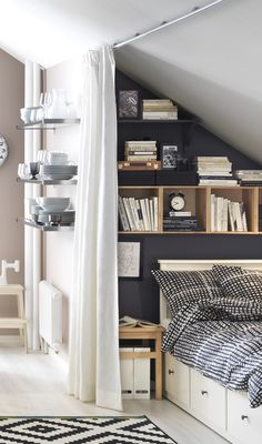Bedroom: Grey walls with wooden box shelves + white bed with black and white patterned bedspreads in a nook + white walls and floors + black and white patterned rug