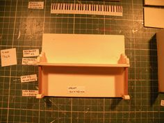 Miniature Piano workshop. Step no.10  Gently place the keyboard on top of the legs and tighten to the front surface as shown on the picture.