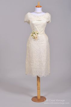 Designed in the 50's, this lovely vintage wedding dress is done in a floral lace over a layer of tulle and is lined in acetate. The bodice features an attached shawl collar, which drapes over the smal