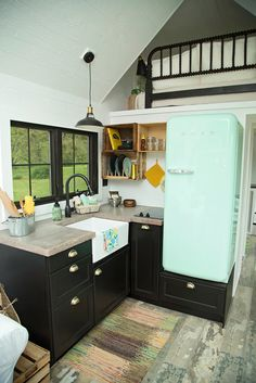 The kitchen has a handcrafted concrete countertop, farm sink, and SMEG retro style refrigerator.