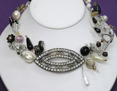 An  antique rhinestone shoe buckle forms the center of this dramatic necklace. It is enhanced with pearls, jet and crystals.