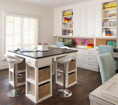 This playful kids space features an office environment centered around a custom designed craft table with ample storage for supplies. White cabinetry contrasts with black tabletop and dark stained hardwood flooring.
