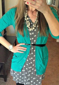 Turquoise cardigan over grey and white polka-dotted shirt dress, black belt, pearls, dark jeans