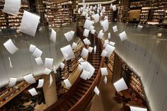 tomoko ikegai / ikg inc illuminates chinese bookstore with fluttering sheets of paper designboom Bookstore Design, Mirror Ceiling, Commercial Complex, Hotel Lounge, Dramatic Lighting, Spiral Staircase, Modern Buildings, Beautiful Buildings, Cultura Pop